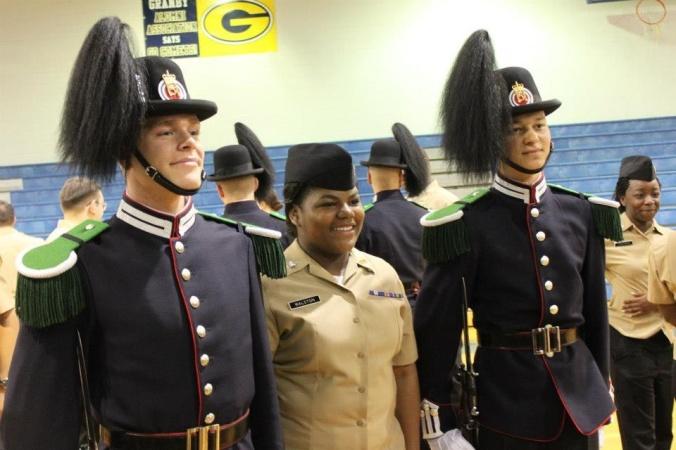 Gardist Eide og gardist Mathisen poserer sammen med en elev ved skolen.